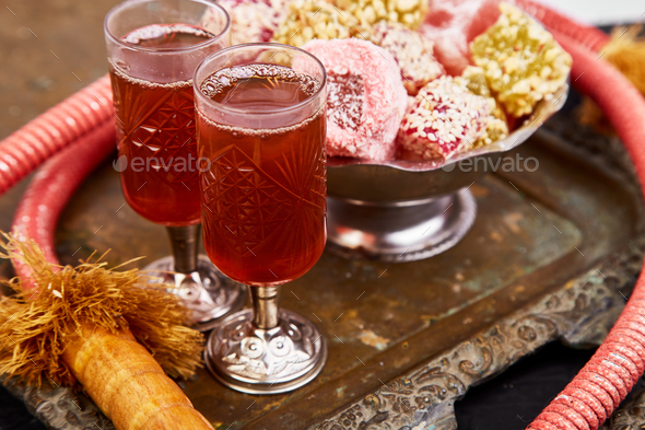 Set of various Turkish delight in bowl on metal tray near hookah tube - Stock Photo - Images
