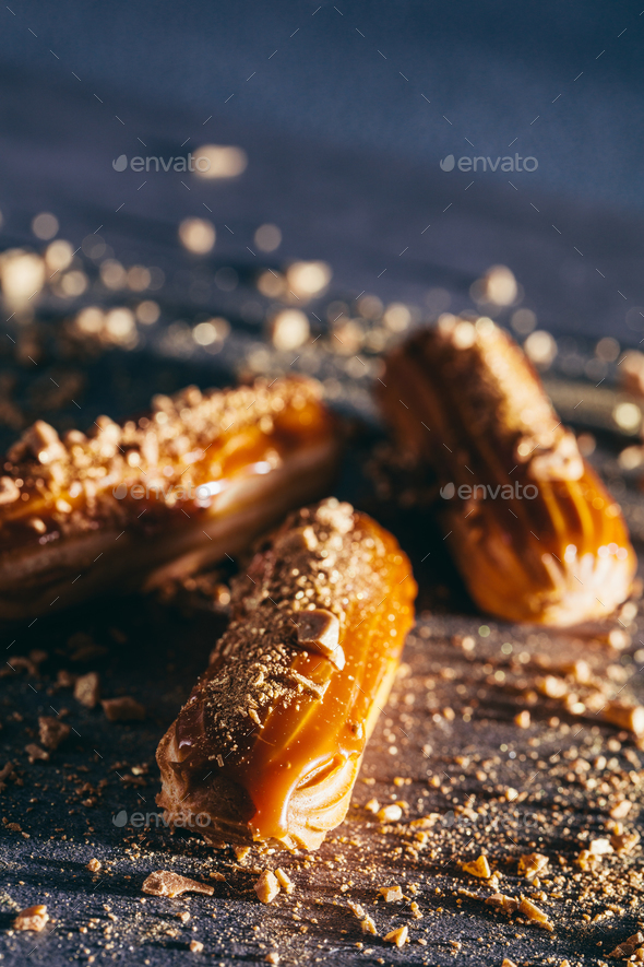 Sprinkled caramel and gold eclairs on dark background. - Stock Photo - Images