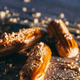 Sprinkled caramel and gold eclairs on dark background. - PhotoDune Item for Sale