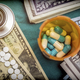Boat of capsules of white and blue next to a wad of banknotes Americans, conceptual image - PhotoDune Item for Sale