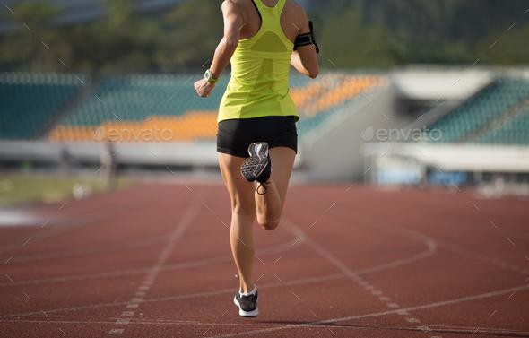RunningSportswoman running on stadium - Stock Photo - Images