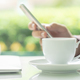 Male hands holding smart phone and cup of coffee on the table - PhotoDune Item for Sale