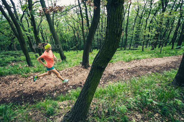 Young woman running in green forest. Endurance sport. - Stock Photo - Images