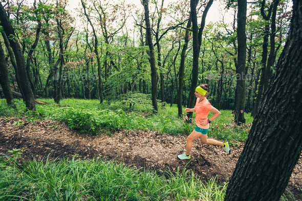 Young woman trail running in mountains on forest trail, sunny da - Stock Photo - Images