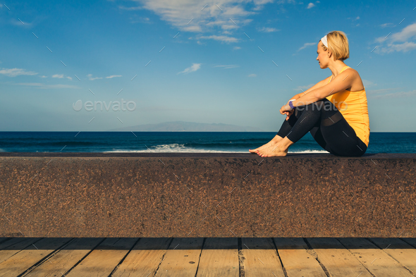 Yoga girl meditating and relaxing in yoga pose, ocean view - Stock Photo - Images