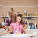 Mother showing daughter how to cook in domestic kitchen - PhotoDune Item for Sale