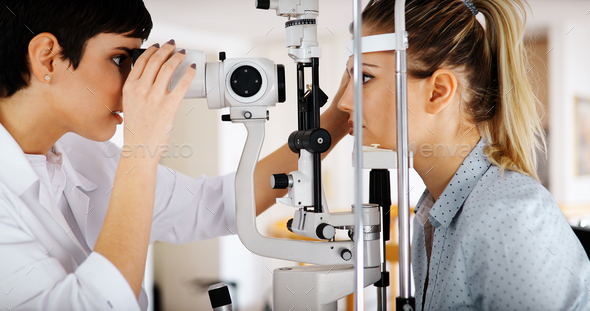 Optometrist examining patient in modern ophthalmology clinic - Stock Photo - Images