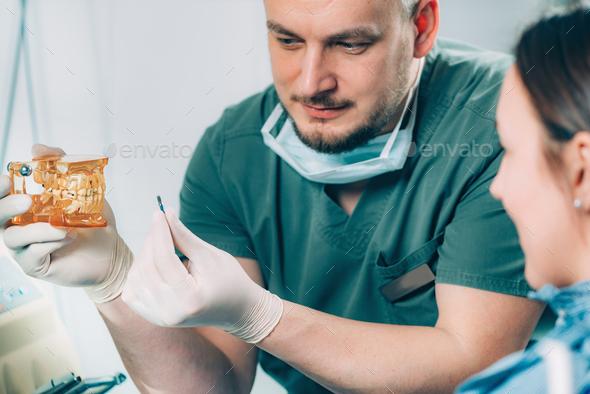 Dentist explaining dental implant procedure to patient - Stock Photo - Images