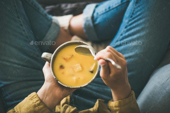 Female keeping mug of warming pumpkin yellow cream soup - Stock Photo - Images