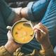 Female keeping mug of warming pumpkin yellow cream soup - PhotoDune Item for Sale