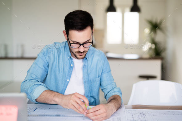 Architect working on plans at home office table - Stock Photo - Images
