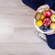 Girl holding white plate with apples, plums, kiwi and pomegranate.  - PhotoDune Item for Sale