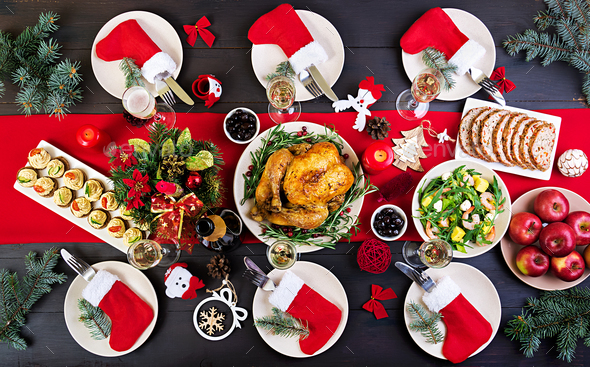 The Christmas table is served with a turkey, decorated with bright tinsel and candles - Stock Photo - Images