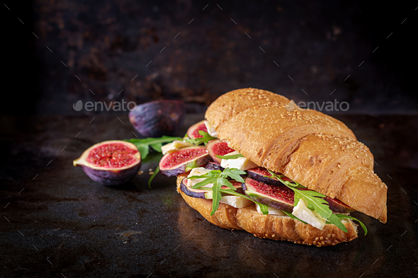 Fresh croissant sandwich with  brie cheese arugula and figs. Delicious breakfast.  Tasty food. - Stock Photo - Images