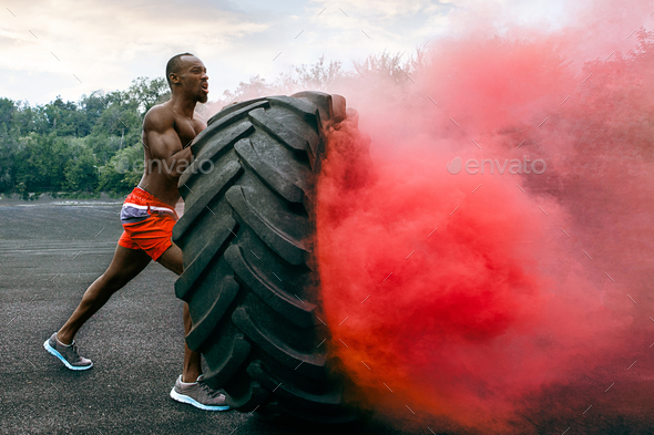Handsome muscular man flipping big tire outdoor. - Stock Photo - Images