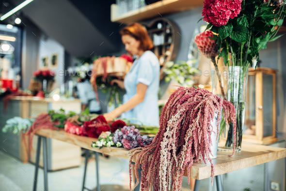Florist making flowers arrangement in shop - Stock Photo - Images