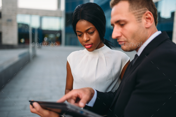 Business woman and businessman looks on laptop - Stock Photo - Images