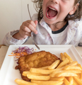 Little Italian girl eating breaded meat and french fries - PhotoDune Item for Sale