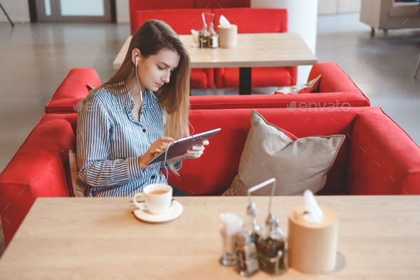 Candid image of young woman using tablet computer in a cafe - Stock Photo - Images