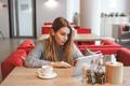 Surprised armenian girl in cafe using tablet - PhotoDune Item for Sale