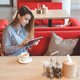 Candid image of young woman using tablet computer in a cafe - PhotoDune Item for Sale