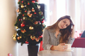 Girl drinking coffee sitting near a Christmas tree in cafe - PhotoDune Item for Sale