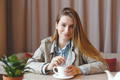 Beautiful young woman with coffee cup looking away at coffeeshop - PhotoDune Item for Sale