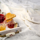 Winter concept with knitted blanket and hot tea with waffer, jam, honey on wooden tray on te bed - PhotoDune Item for Sale