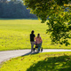 City park, Munich, Germany. View of a young couple with a baby cart walking on a path - PhotoDune Item for Sale