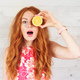 Excited young woman holding covering eyes with two slices of lemons - PhotoDune Item for Sale