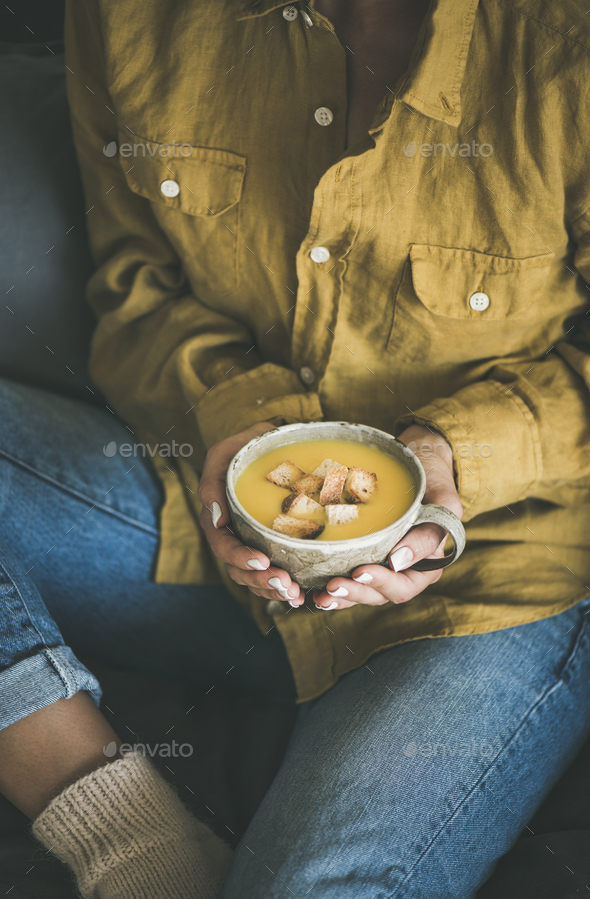 Woman sitting and holding warming pumpkin soup in mug - Stock Photo - Images