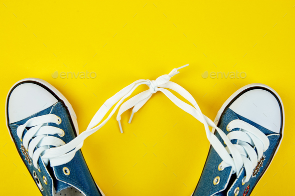 Blue female or male sneakers on yellow paper background - Stock Photo - Images