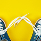 Blue female or male sneakers on yellow paper background - PhotoDune Item for Sale