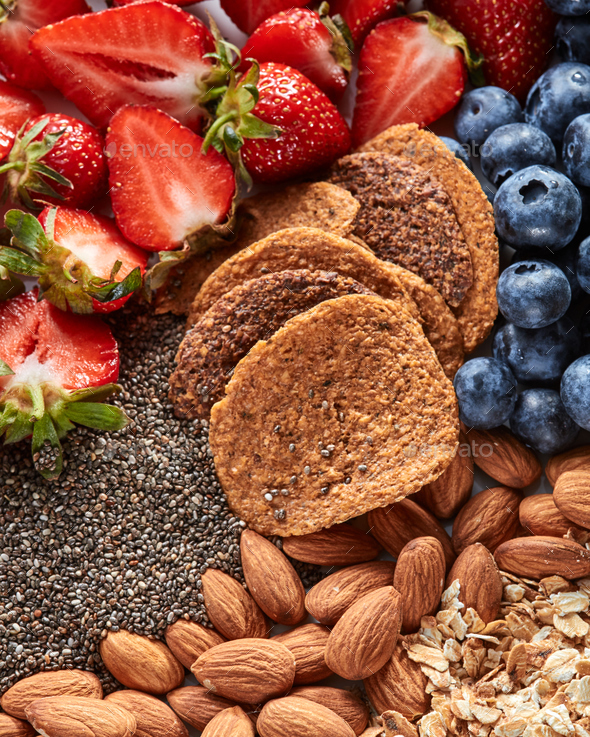 Fresh organic ingredients for dietary homemade natural breakfast - berries, granola, nuts, chia - Stock Photo - Images