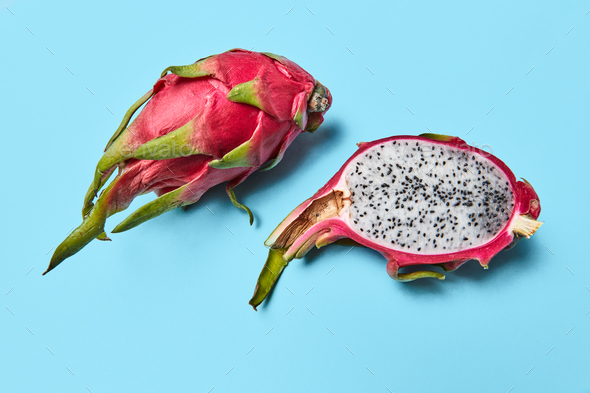 A dragon fruit, or pitahaya represented on a blue background with a copy space. Ripe tropical fruit - Stock Photo - Images