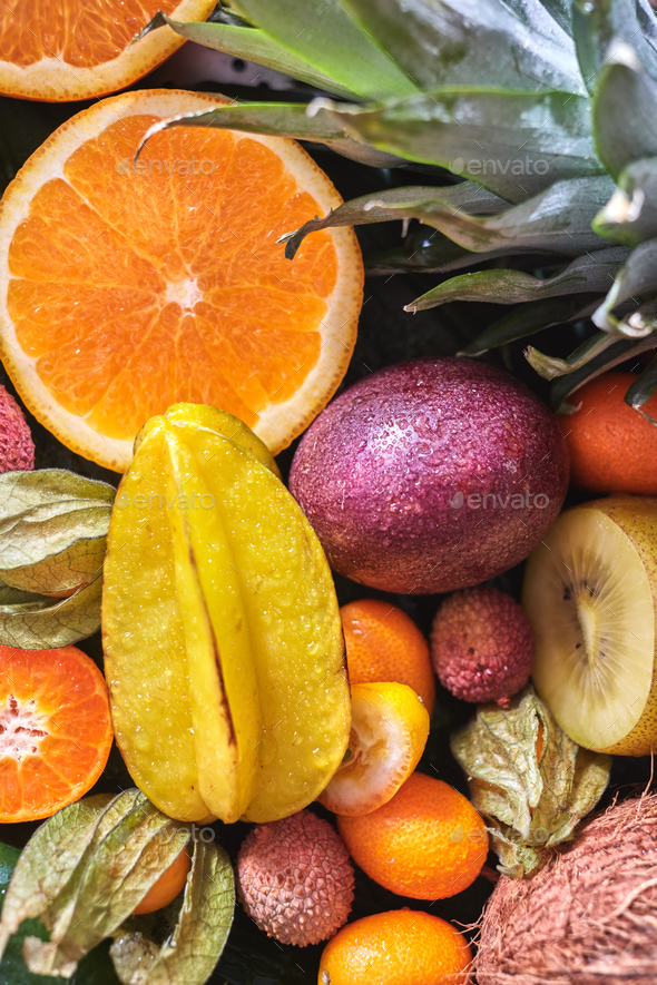Natural organic background from exotic fruits carambola, half of orange, passion fruit, pineapple - Stock Photo - Images