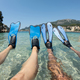 Snorkeler couple relaxing on the beach. Tanned legs in blue fins, flippers - PhotoDune Item for Sale