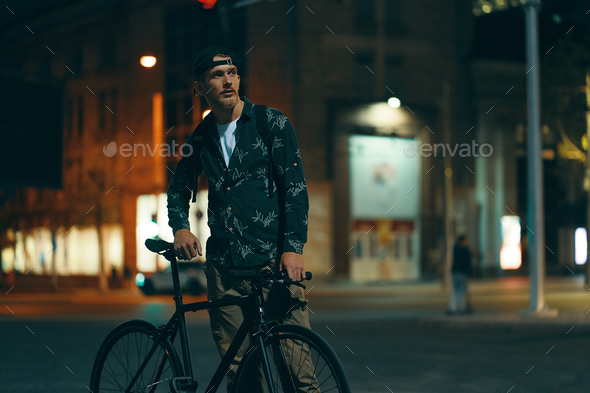 Cyclists standing on the road aside his classic bike while watch - Stock Photo - Images