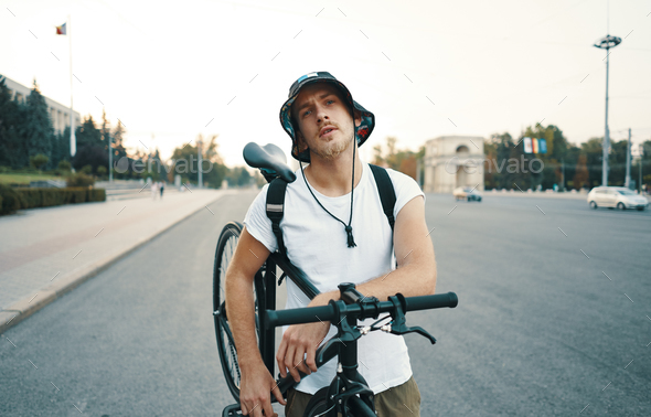 Portrait of a blonde white man in the city with a classic bike o - Stock Photo - Images