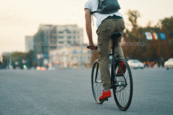 Closeup of casual man legs riding classic bike on city road - Stock Photo - Images