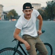 A Young, handsome man posing while sitting on bike, on city road - PhotoDune Item for Sale