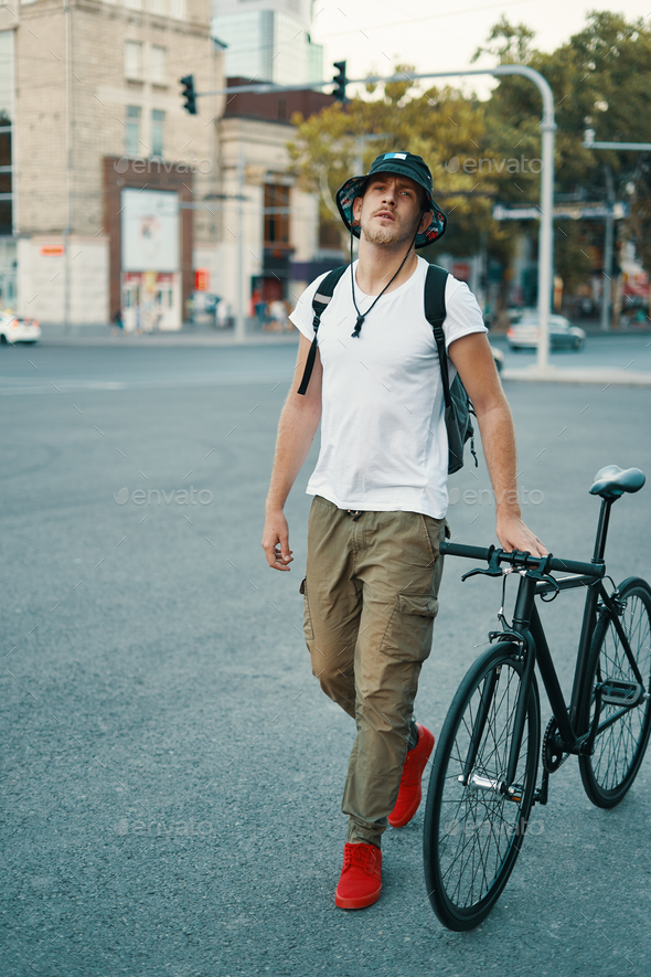 Portrait of young man walking with thoughtfully classic bicycle - Stock Photo - Images