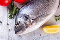 Fresh sea fish with spices and lemon ready for cooking . Dorado or sea bream fish on wooden - PhotoDune Item for Sale