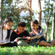 Three asian boy and girls read book in garden. - PhotoDune Item for Sale
