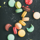 Flat-lay of sweet colorful French macaroons over black background - PhotoDune Item for Sale