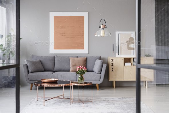 Flowers On Copper Table In Front Of Grey Couch Living Room Stock Photo