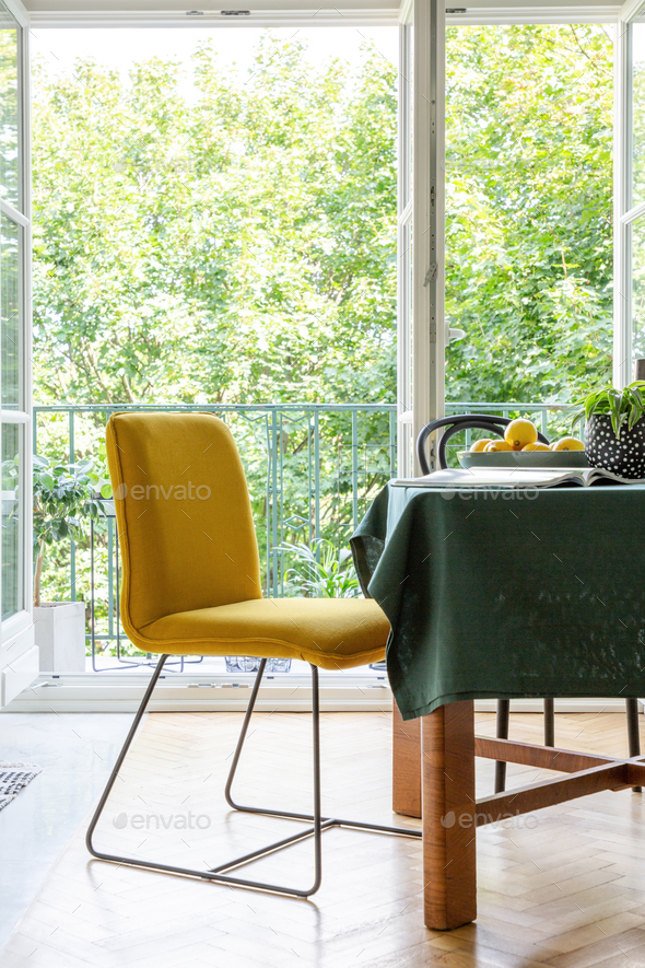 Yellow chair next to a table in a dining room interior with a te - Stock Photo - Images