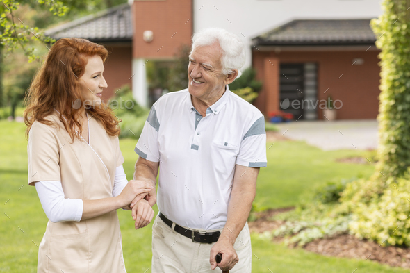 Smiling grey-haired senior man with a walking stick talking talk - Stock Photo - Images