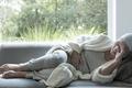Sick woman with a headache lying on a sofa - PhotoDune Item for Sale