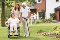 An elderly disabled couple with their caretaker in the garden ou - PhotoDune Item for Sale